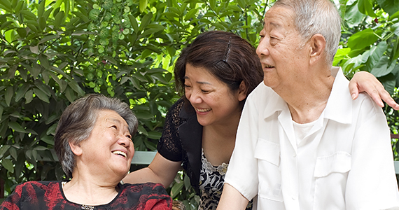 A happy older Asian couple and their daughter