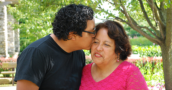 Latino son kissing his mother