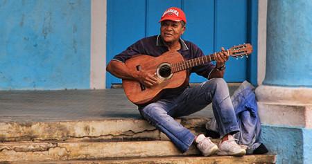 Old Cuban man plays guitar
