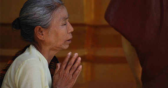 Older Asian woman praying