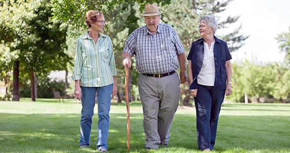 Three Latino seniors walking in park during the day