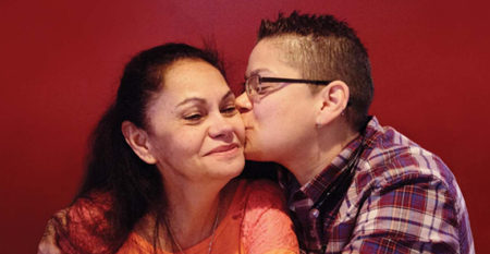 Latino woman being kissed on the cheek by her caregiver