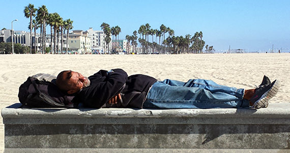 Homeless man lying down on concrete slab on Venice beach