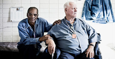 Older black prisoner and older white prisoner in prison cell