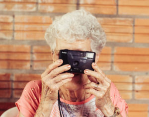 Older woman taking photograph with camera