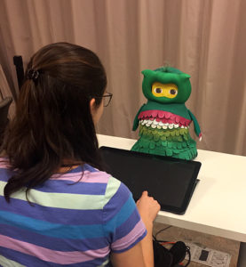 Student interacting with robot on table