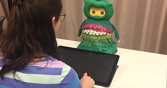 Student interacts with SPRITE robot on table top