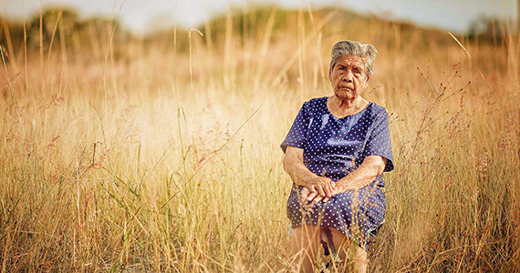 Older Latino woman sits in a field