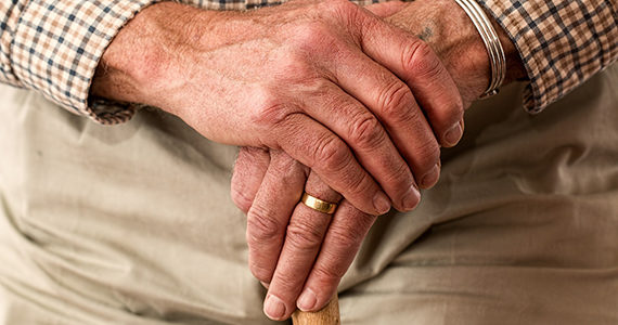 Photo zoomed in on old man's hand holding his cane.