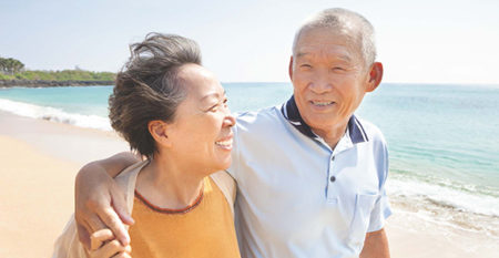 older asian couple walks on the beach