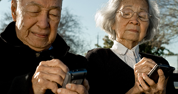 Older Asian couple using their mobile phones