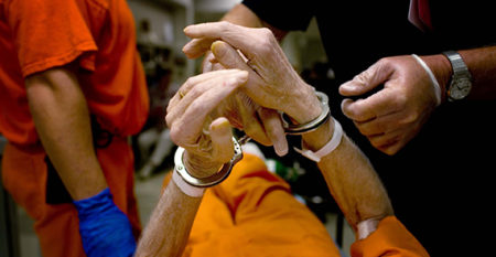 Aging inmate with handcuffs being treated