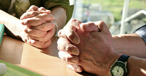 Hands of two people praying together