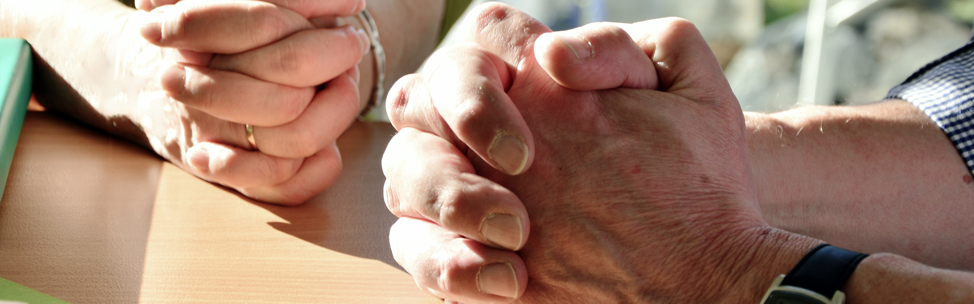 Hands of two people praying on a table