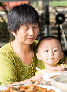Asian grandmother feeding her grandson