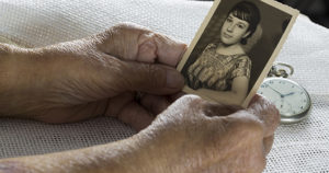 Older woman holding old photo of herself when she was young