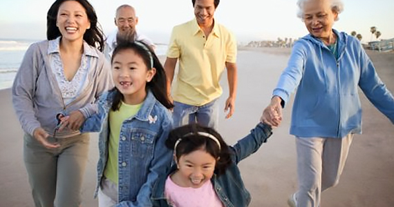 Asian multi-generational family walking and playing on the beach