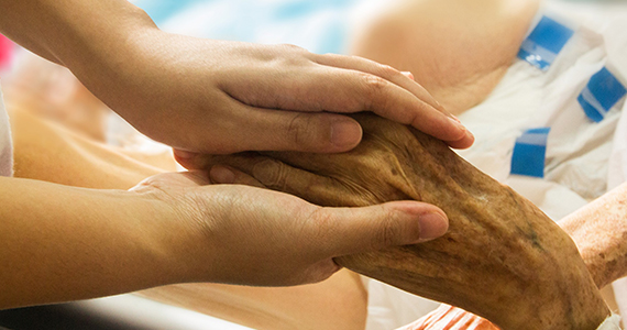 someone holding hands of a hospice patient