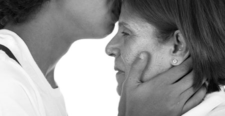 Son kissing mother's forehead