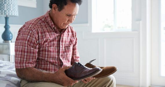 Senior Hispanic Man Suffering With Dementia Trying To Dress