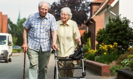 older couple walking on neighborhood sidewalk