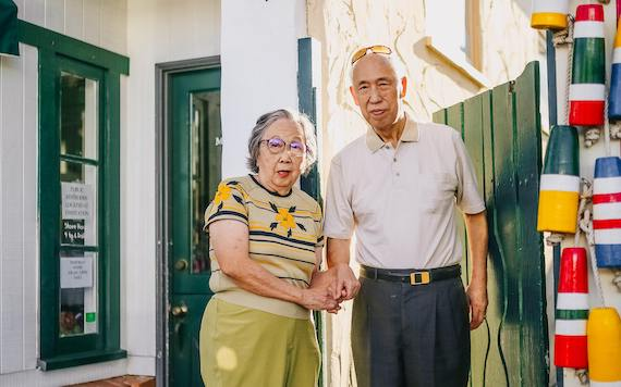 an elderly Pacific Islander man and woman standing on a colorful street corner