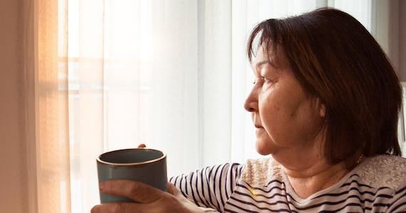 a women holding a cup of coffee while looking out a window